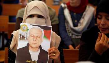 A Palestinian woman holds a portrait of a relative being held in an Israeli jail in front of the International Committee of the Red Cross, in Gaza City, October 2019.