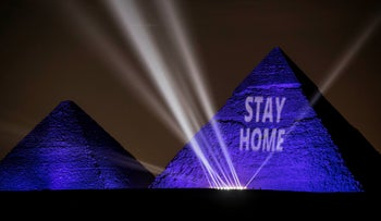 """The Great pyramids lighten-up with blue light and reading with a laser projection the message """"Stay Home"""" on the Giza plateau outside Cairo, April 18, 2020."""