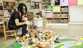 A teacher cleans toys to prepare for reopening at a preschool in Jerusalem, May 6, 2020.