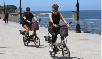 People wearing protective face masks ride on bicycles along Beirut's seaside Corniche as Lebanon begins to ease its nationwide lockdown, May 4, 2020.