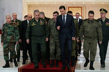 Syrian President Bashar Assad, center right, speaks with Russian Defense Minister Sergei Shoigu, center left, before their meeting in Damascus, Syria, Monday, March 23, 2020.