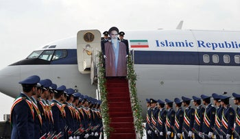Iranian air force soldiers carry a cardboard cut out of late founder of Islamic Republic Ayatollah Ruhollah Khomeini, down the stairs of a passenger plane at Merhrabad airport, February 1, 2012.