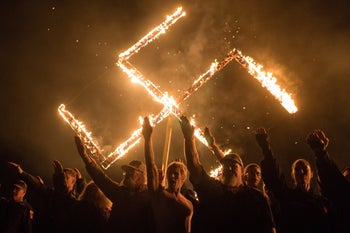 Supporters of the National Socialist Movement, a white nationalist political group, give Nazi salutes while taking part in a swastika burning at an undisclosed location in Georgia, United States.