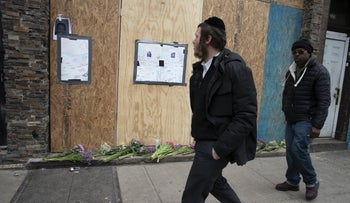 An Orthodox man passing the boarded-up kosher grocery store in Jersey City, where three people were killed days earlier, December 13, 2019.