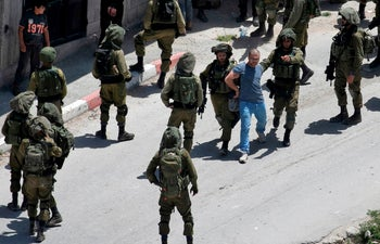 Israeli soldiers detain a Palestinian man in the village of Yabad near the West Bank city of Jenin, May 12, 2020
