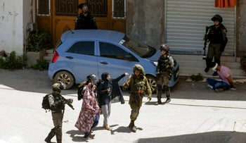 Israeli soldiers detain a Palestinian man in the village of Yabad near the West Bank city of Jenin on May 12, 2020,