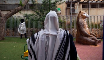 Ultra-Orthodox Jews pray at a playground next to their homes as synagogues are closed to help stop the spread of the coronavirus, in Bnei Brak, Israel, April 24, 2020