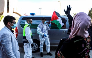 Amir Naji, 18, waves a Palestinian flag while clad in a surgical mask and gloves after being released at a checkpoint near the city of Ramallah, West Bank, April 14, 2020.