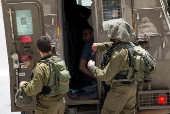 Israeli soldiers arrest a Palestinian after a soldier was killed during an arrest raid, in the village of Ya'bad near the West Bank city of Jenin, May 12, 2020.