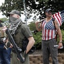 People holding weapons stand on a street corner in Raleigh, N.C., Friday, May 1, 2020. About a dozen demonstrators marched Friday afternoon around the area of the Old Capitol, Legislative Building and Executive Mansion. Several had visible firearms. It was not immediately clear what specific issues they were protesting, as none carried signs