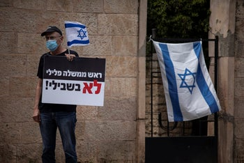 """A protester holding a placard stating """"Criminal Prime Minister not for me,"""" during a demonstration against Benjamin Netanyahu serving as premier while facing criminal indictments, outside the prime minister's residence in Jerusalem, May 3, 2020."""