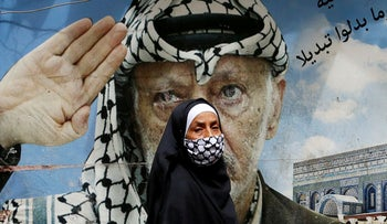 A woman walks past a poster depicting late Palestinian leader Yasser Arafat in Beirut's Shatila Palestinian refugee camp. Lebanon, March 30, 2020