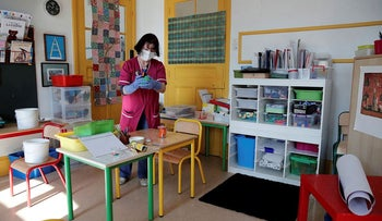 A school staff member cleans school supplies in a classroom at a primary school during its reopening in Paris, May 14, 2020