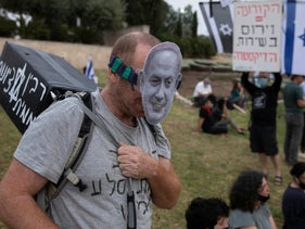 An Israeli man wears a mask depicting Israeli Prime Minister Benjamin Netanyahu during a demonstration outside the Knesset, May 14, 2020