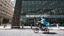 A food delivery cyclist wearing a mask goes past the Tel Aviv Stock Exchange, March 2020.