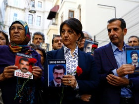 Pervin Buldan, co-leader of the pro-Kurdish Peoples' Democratic Party (HDP), holds her husband Savas Buldan's portrait as she takes part in a protest against police detentions, Istanbul, Turkey November 2, 2019.