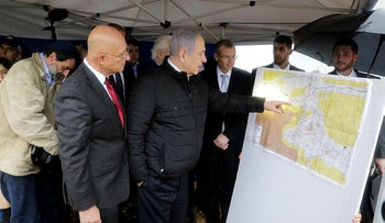 Israeli Prime Minister Benjamin Netanyahu checks the area map during visit to Ariel settlement in the West Bank, February 24, 2020.