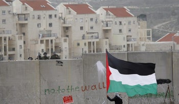A protester in Bilin waving a Palestinian flag in front of Israeli troops during a protest against the West Bank separation barrier. The Israeli settlement of Modi'in Ilit is seen in the background.