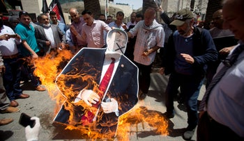 Palestinians burn a cutout of the U.S. Secretary of State Mike Pompeo, during a protest against his visit to Israel in the West Bank city of Nablus, May 23, 2020.