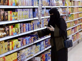 A Saudi woman wearing protective gloves shops at a supermarket in Riyadh, Saudi Arabia, May 11, 2020.