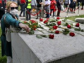 A protester places a rose at the World War Two monument during a protest against a mass for the Nazi collaborators, in Sarajevo, Bosnia and Herzegovina, May 16, 2020.