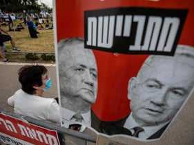 "A demonstrator sits with a sign reading ""ashamed"" at a protest against the Netanyahu-Gantz unity government in Jerusalem, May 14, 2020."