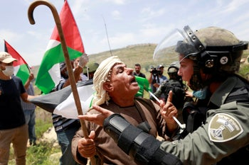 A Palestinian man argues with an Israeli border policewoman during a protest marking the 72nd anniversary of Nakba and against Israeli plan to annex parts of the occupied West Bank, in the village of Sawiya near Nablus, May 15, 2020.