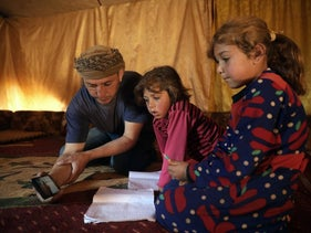 Tariq al-Obeid, displaced from the eastern countryside of Idlib, Syria, shows a lesson for his children on a mobile phone in Kelly, a town in northern Idlib, April 13, 2020.