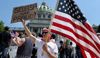 A Trump supporter holds a U.S. flag during a protest against COVID-19 restrictions outside the Pennsylvania State Capitol Building in Harrisburg, Penn. May 15, 2020
