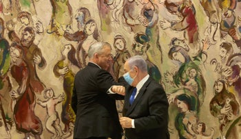 Benny Gantz (L) and Benjamin Netanyahu bump elbows after their unity government was sworn in in the Knesset, Jerusalem, May 17, 2020.