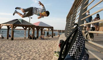 A child performs parkour during a heat wave on Hilton Beach, Tel Aviv, May 17, 2020.