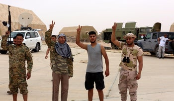 Members of Libya's internationally recognized government flash victory signs after taking control of Watiya airbase, southwest of Tripoli, Libya, May 18, 2020.