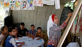 A Palestinian school girl Fajr Hmaid, 13, teaches her neighbours' children an Arabic language lesson as schools are shut due to the COVID-19 restrictions, at her family house in Gaza, May 19, 2020.