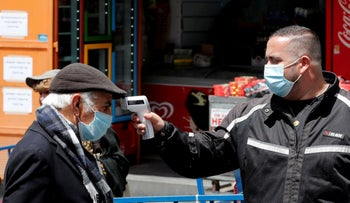 A shopper wears a face mask as he gets his body temprature checked, Jerusalem April 26, 2020