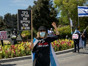 Protestors protest against Prime Minister Benjamin Netanyahu serving as prime minister while facing criminal indictments in front of Israel's Parliament in Jerusalem, April 30, 2020.