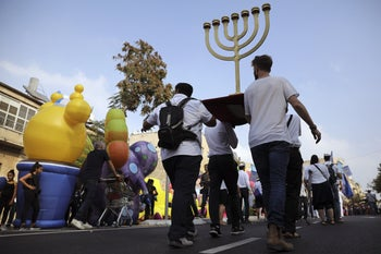 People carrying a menorah as they participate in an annual support march for Israel in Jerusalem, October 17, 2019.