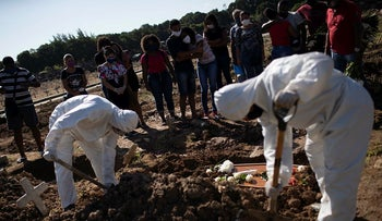 Relatives watch cemetery workers shovel dirt over the casket of 22-year-old COVID-19 victim Amanda da Silva at the Caju cemetery in Rio de Janeiro, Brazil, Wednesday, May 20, 2020