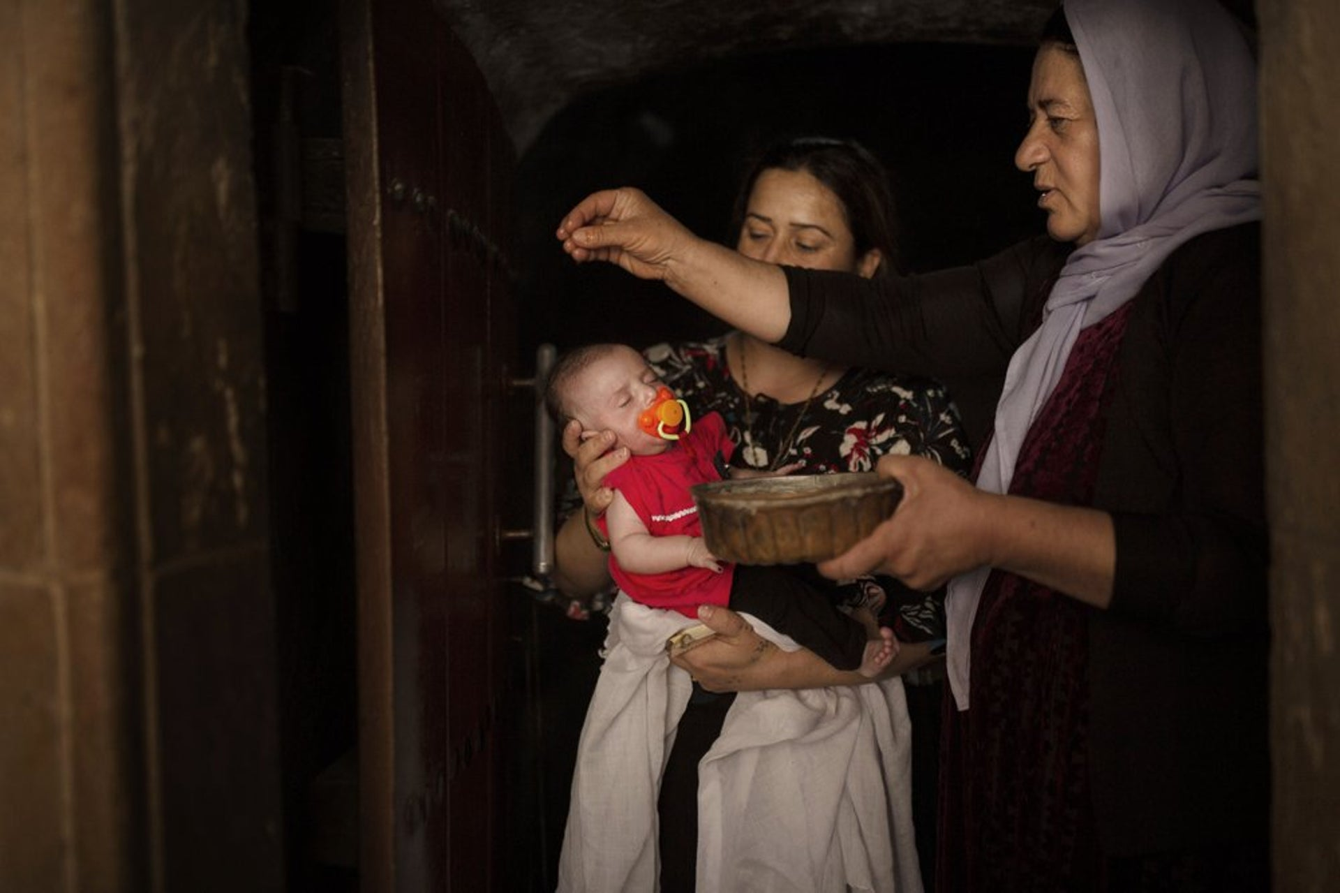 A baby girl is anointed with water from an ancient spring by a Yazidi holy woman at the Lalish temple near Sheikhan, Iraq.