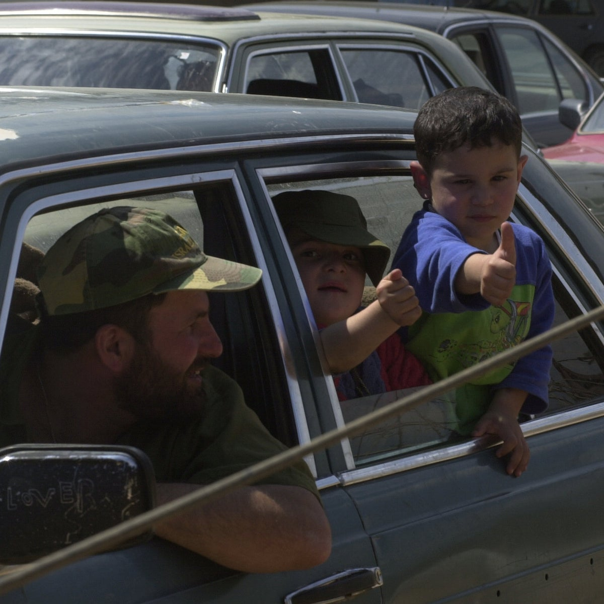 A youngster giving a thumbs-up sign as members of the South Lebanon Army and their families seek to gain entry into Israel, May 23, 2000.