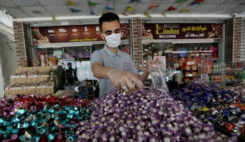 A worker packs sweets outside a shop in Khan Younis in the southern Gaza Strip, May 19, 2020.