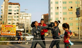 Palestinian girls, instructed by their coach Osama Ayob, participate in a boxing training session at the sidewalk of a beach, in Gaza City May 21, 2020.