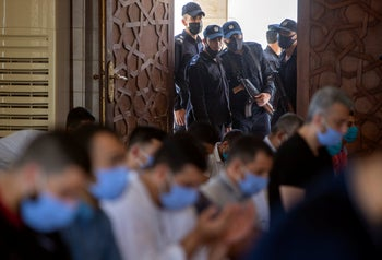 Hamas police stand guard at the entrance of a mosque as worshipers attend the last Friday noon prayer of the holy month of Ramadan, in Gaza City, May. 22, 2020.