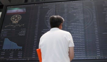 A man looks at electronic board showing stock prices, following the outbreak of the coronavirus , at Tehran Stock Exchange in Tehran, Iran, May 12, 2020.