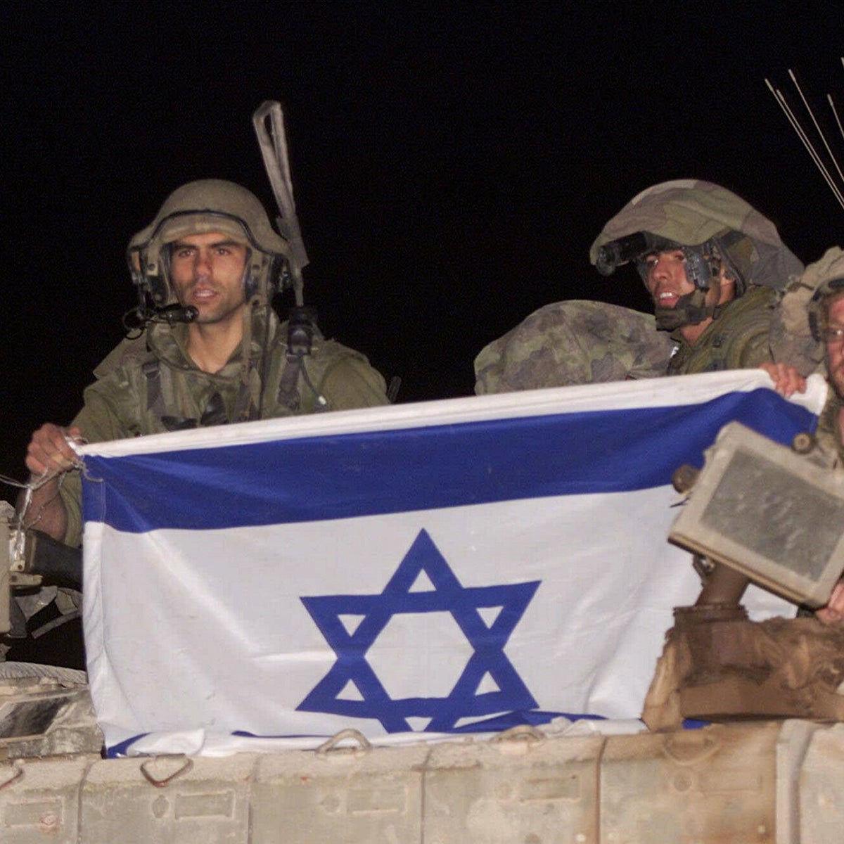 Israeli soldiers ride atop their armored vehicle holding an Israeli flag as they withdraw from south Lebanon into Israel, at the Israeli-Lebanese border near Metula, May 24, 2000.