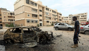 A fighter loyal to Libya's U.N.-recognized government stands next to a destroyed car following in Tripoli on May 9, 2020.