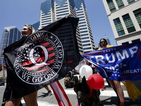 Pro-Trump protestors against the California coronavirus lockdown hold a QAnon conspiracy banner with its acronym 'WWG1WGA,' standing for 'Where we go one, we go all.' San Diego, May 01, 2020