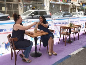 Two diners sit outside a restaurant in Tel Aviv in a dining area that used to be a parking spot.