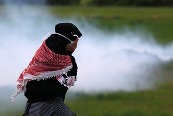 A Palestinian woman covers her face from tear gas, fired by Israeli forces as they protest against U.S. President Donald Trump's Mideast initiative, near a Jewish settlement Beqa'ot in Jordan Valley in the West Bank, Feb. 2020.