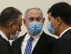 Netanyahu consults with his lawyers at the Jerusalem District Court on the first day of his trial, May 24, 2020.