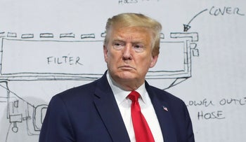 U.S. President Donald Trump pauses in front of a diagram while touring the Ford Rawsonville Components Plant, repivoted towards ventilators and medical supplies, in Ypsilanti, Michigan, U.S., May 21, 2020